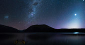 Panorama, Amanzing Starry night at Lake Rotoiti. Reflection of the Milky way and galaxy on the lake. Nelson Lake National Park, New Zealand. High ISO Photography.