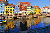 24.08.2019. Panorama and cityscape of Nyhavn water canal with young woman, colorful facades of old houses and old ships in the Old Town of Copenhagen,  Denmark.