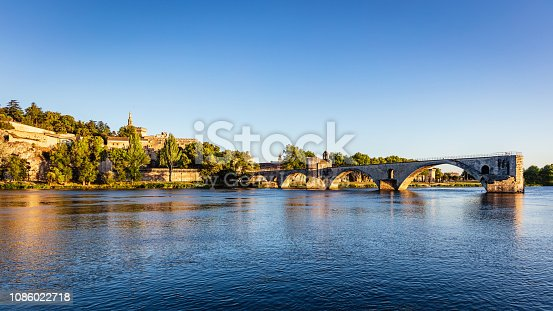 Panorama of famous Avignon Bridge, so-called Pont d'Avignon or Pont Saint Benezet with Popes Palace in the background in warm late afternoon light before sunset. Avignon, France, Europe.