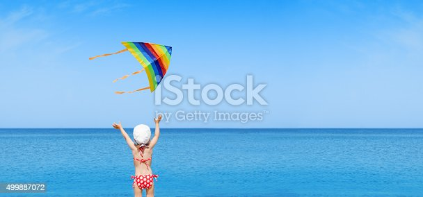istock panorama child play flying kite on beach 499887072
