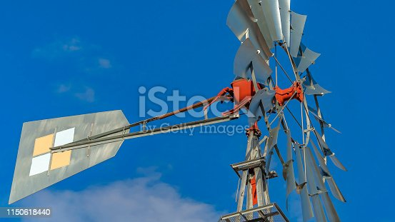 Panorama Close up of a windpump with vibrant blue sky and puffy clouds in the background. This multi-bladed windpump is a type of windmill used for pumping water.