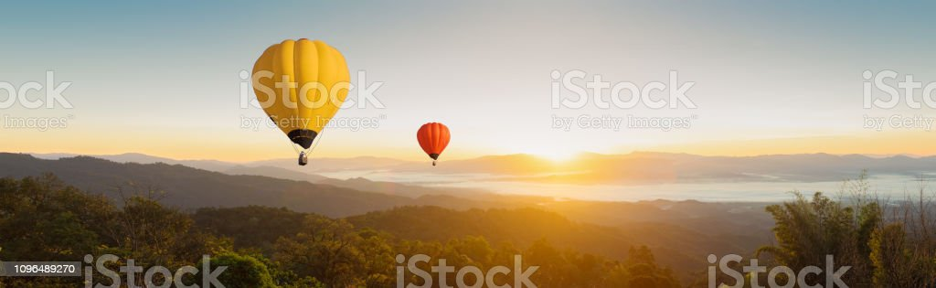 Panorama Colorful balloons floating in the sky in the mountain landscape in the morning Panorama Colorful balloons floating in the sky in the mountain landscape in the morning Adventure Stock Photo