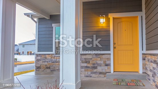 Panorama Entryway of a home with stairs going up to the front porch and door. Rectangular pillars, stone brick wall, and horizontal siding defines the facade of this home.