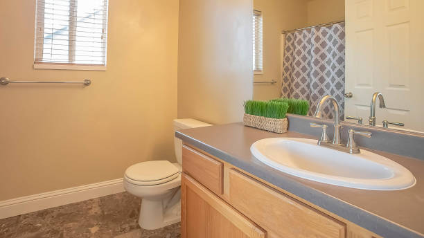 Panorama frame Bathroom interior with close up of sink cabinet and mirror beside the toilet stock photo