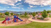 Panorama frame Park and playground wth a scenic view of Mount Timpanogos towering over a lake. Homes and trees can also be seen under the blue sky and puffy clouds.