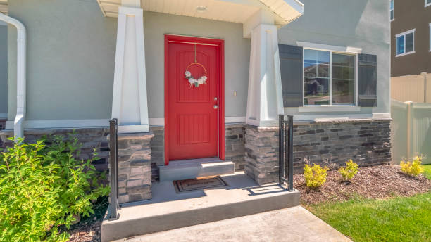 Panorama frame Piched roof over the vivid red front door with pillars and railing on both sides Panorama frame Piched roof over the vivid red front door with pillars and railing on both sides. Small porch at the entrance of a home with gray concrete and stone brick wall. front door stock pictures, royalty-free photos & images