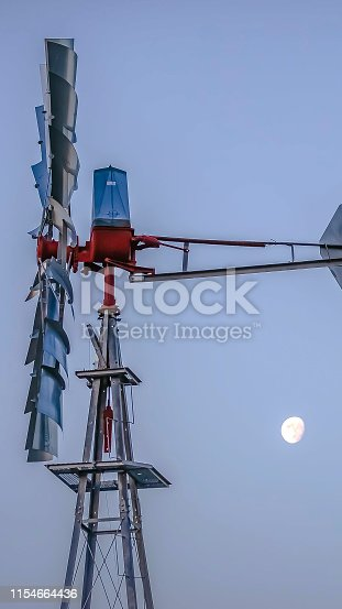 Panorama frame Side view of a windpump with moon and sky in the background. The shiny steel blades and tail of the windpump are connected to the red rotor hub.