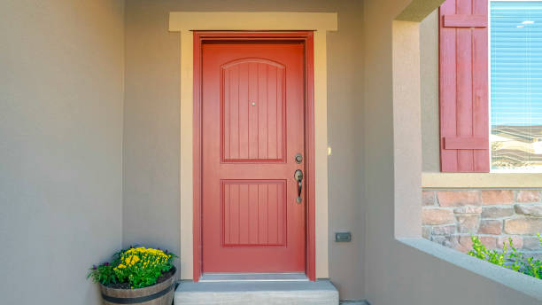 Panorama frame The red front door of a house with concrete exterior wall and shutters on window Panorama frame The red front door of a house with concrete exterior wall and shutters on window. Doormat and potted flowers are placed by the doorstep. front door stock pictures, royalty-free photos & images