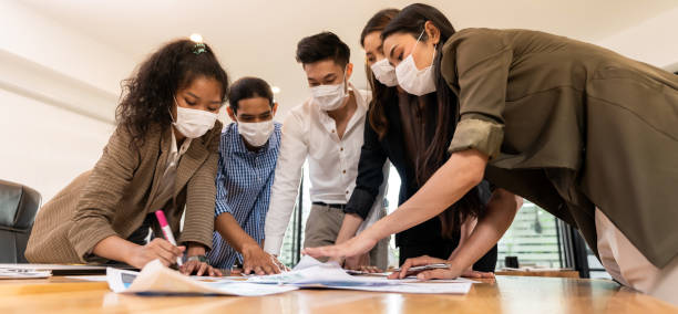 Panorama Interracial business team wear face mask brainstorm at new normal office stock photo