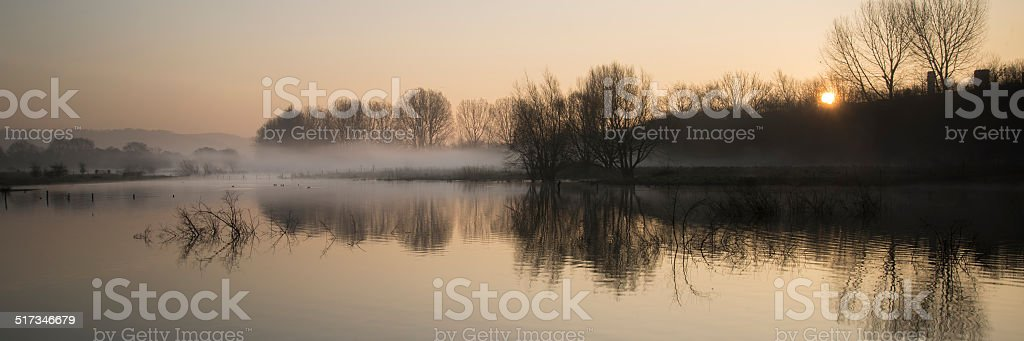 Panorama landscape of lake in mist with sun glow stock photo