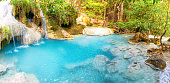 Panorama of emerald blue lake with rock cascades of stream waterfall in tropical jungle forest. Landscape of Erawan National park, Kanchanaburi, Thailand