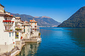 Panorama landscape on beatiful Lake Como in Brienno, Lombardy, Italy. Scenic small town with traditional houses and clear blue water. Summer tourist vacation on rich resort with harbour. Nice swans
