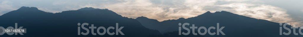 Panorama Berglandschaft in der Silhouette mit wispy bewölktem Himmel in der blauen Stunde – Foto