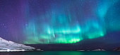 Panorama of colorful northern lights near Tromsö in Norway