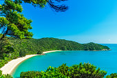 panoramic view of a tropical beach with turquoise water and white sand in abel tasman national park, new zealand