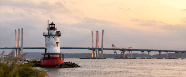 Panorama of a caisson (sparkplug) style lighthouse under soft golden light with a bridge in the background.