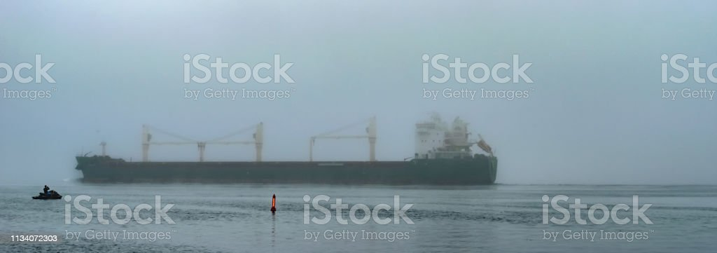 Panorama of a Freight ship in the fog near bouy and watercraft on the St. Lawrence River stock photo