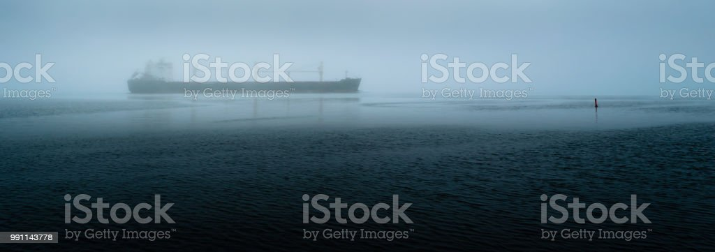 Panorama of a freight ship travelling on a river near a marker bouy during a foggy morning. stock photo