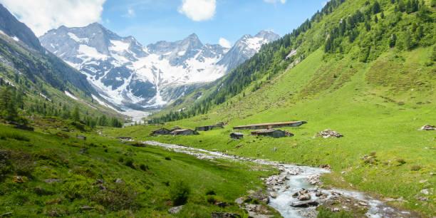 Panorama einer Berglandschaft mit Berghütten und Gletscher im Hintergrund – Foto