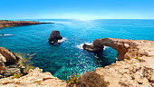 Panorama of a natural landmark Love Bridge. Yellow stone cliffs near transparent crystal clear amazing sparkly water and froth. Warm cloudless summer day. Feeling of wanderlust, Agia Napa, Cyprus
