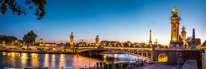 Panoramic view at twilight time of the day of the iconic bridge Alexandre III in the center of Paris in France. In the background, we can also see the Eiffel Tower and Les Invalides monuments.