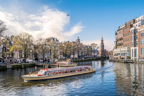 panorama van amsterdam met toeristische boot, nederland - westerkerk stockfoto's en -beelden