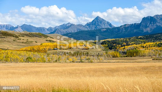 Panoramic autumn mountain valley view at the base of Mount Sneffels, 14,158-ft (4,315m), the highest peak in its namesake Sneffels Range of the San Juan Mountains, part of the Rocky Mountains of North America. Mt. Sneffels is also the high peak in Ouray County of southwestern Colorado, USA.