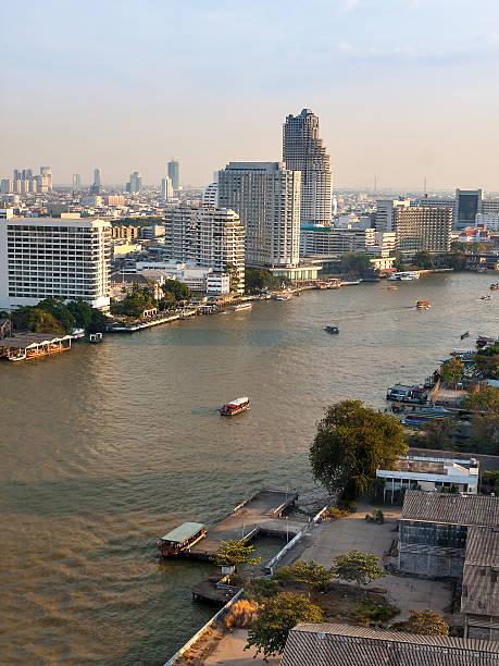 Panorama of Bangkok with the river and boats at sunset.