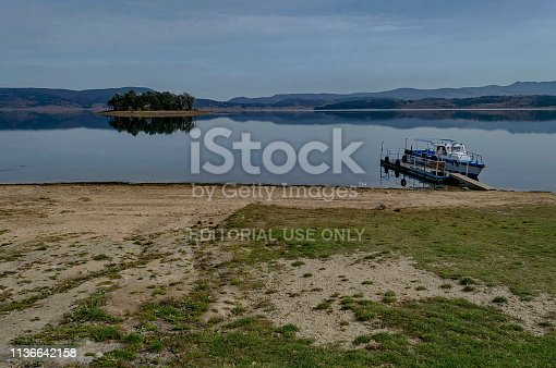 istock Panorama of Batak dam reservoir with island and passenger-ship in the water, coastal autumn glade, forest, hill at Rhodope mountains 1136642158