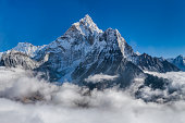 XXXXL size panorama of Mount Ama Dablam - probably the most beautiful peak in Himalayas. \n This panoramic landscape is an very high resolution multi-frame composite and is suitable for large scale printing\nAma Dablam is a mountain in the Himalaya range of eastern Nepal. The main peak is 6,812  metres, the lower western peak is 5,563 metres. Ama Dablam means  'Mother's neclace'; the long ridges on each side like the arms of a mother (ama) protecting  her child, and the hanging glacier thought of as the dablam, the traditional double-pendant  containing pictures of the gods, worn by Sherpa women. For several days, Ama Dablam dominates  the eastern sky for anyone trekking to Mount Everest basecamp