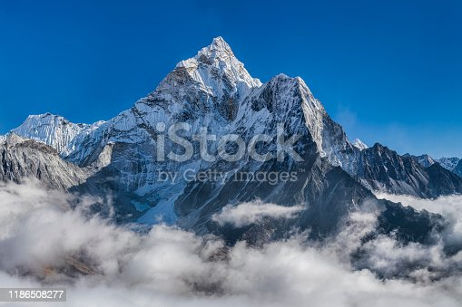 XXXXL size panorama of Mount Ama Dablam - probably the most beautiful peak in Himalayas.   This panoramic landscape is an very high resolution multi-frame composite and is suitable for large scale printing Ama Dablam is a mountain in the Himalaya range of eastern Nepal. The main peak is 6,812  metres, the lower western peak is 5,563 metres. Ama Dablam means  'Mother's neclace'; the long ridges on each side like the arms of a mother (ama) protecting  her child, and the hanging glacier thought of as the dablam, the traditional double-pendant  containing pictures of the gods, worn by Sherpa women. For several days, Ama Dablam dominates  the eastern sky for anyone trekking to Mount Everest basecamp