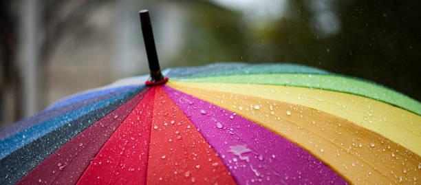 panorama of close-up  umbrella in rainbow colors in rainy autumn day, blur focus - umbrellas stock photos and pictures