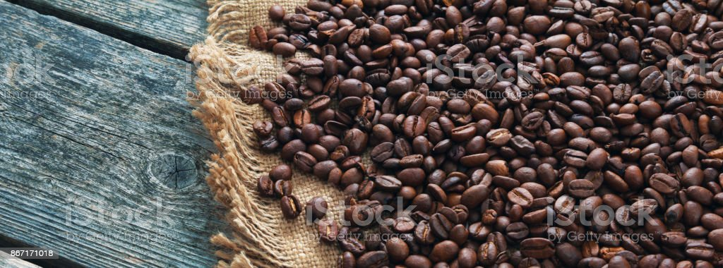 Panorama of coffee roasted grains on jute and wooden boards stock photo