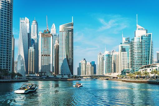 Panorama of Dubai Marina in UAE, modern skyscrapers and port with luxury yachts.