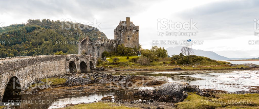 Panorama of Eilean Donan castle with Scottish flag stock photo