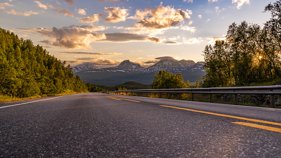 This image shows sunset Panorama of empty winding country road in Norway, Europe, Scandinavia. Auto travel on sunset. Blue sky with clouds and mountains. Lofoten islands.