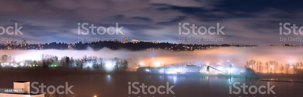 Panorama of fog covering city and river at night stock photo