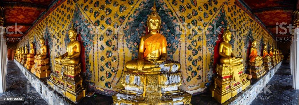 Panorama of Golden buddha image at corridor in Wat Arun Ratchawararam Ratchawaramahawihan or Temple of Dawn in bangkok thailand. This is beautiful row of golden buddha image in the temple of thailand. stock photo