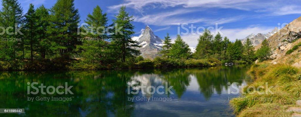 Panorama of Green alpine with the Grindjisee lake and Matterhorn peak reflecting in water,one of the lakes on the 5 lake route near,Zermatt,Valais region,Switzerland,Europe Panorama of Green alpine with the Grindjisee lake and Matterhorn peak reflecting in water,one of the lakes on the 5 lake route near,Zermatt,Valais region,Switzerland,Europe Blue Stock Photo