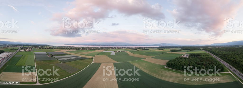 panorama of green fields and lake stock photo
