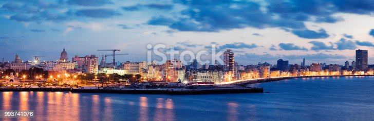 Havana, Cuba skyline at dusk seen from El Morro Fortress. The Malecon seafront promenade and Havana Vieja illuminated at dusk, car light trails are visible on the street, panoramic image created from 4 long exposures, 50 megapixel image.