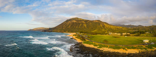Panorama of Koko Head crater taken from a drone in Hawaii with both a rocky and a sandy beach with the incoming surf stock photo