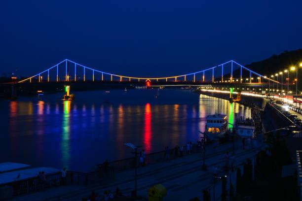 Panorama of Kyiv, Ukraine. Dnipro river, Park bridge and highway. City asphalt road at night, travel background stock photo