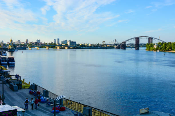 Panorama of Kyiv, Ukraine. Dnipro river, Podilsko-Voskresensky Bridge and Kyiv River Port waterfront stock photo