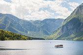 istock Panorama of Lake Bohinj, also called bohinjsko jezero, on a sunny afternoon, with a boat crusing on the waters. Bohinj lake is a major landmark of the Julian Alps mountain chain in Slovenia, Europe. 1326357045