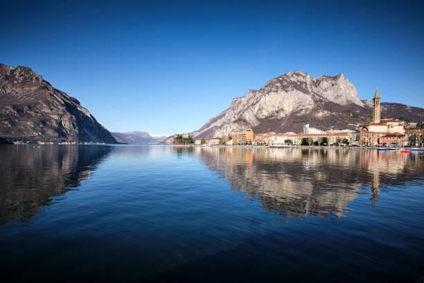 panorama van lecco dat op het meer wordt weerspiegeld - lecco lombardije stockfoto's en -beelden
