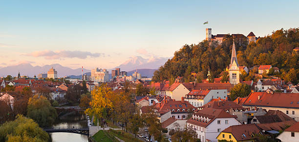 Panorama of Ljubljana, Slovenia, Europe. Cityscape of the Slovenian capital Ljubljana at sunset. Ljubljana castle on hill above town. River Ljubljanica running trough city center. Karavanke mountains in background. Panorama. ljubljana castle stock pictures, royalty-free photos & images