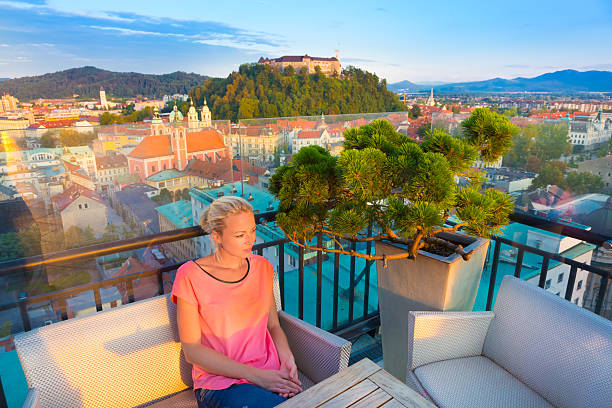 Panorama of Ljubljana, Slovenia, Europe. Female tourist enjoying in rooftop bar with panoramic view of Slovenian capital Ljubljana at sunset. ljubljana castle stock pictures, royalty-free photos & images