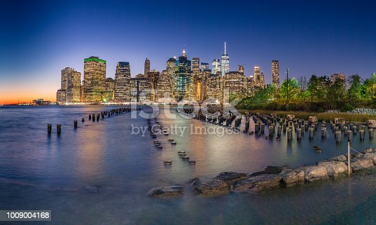 Panorama of NYC at night with wooden posts and the East River in the foreground.