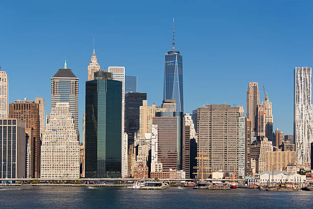 Panorama of Lower Manhattan Skyline with Freedom Tower Lower Manhattan skyline, seen from Brooklyn over the east River with the Freedom Tower and South street seaport. south street seaport stock pictures, royalty-free photos & images